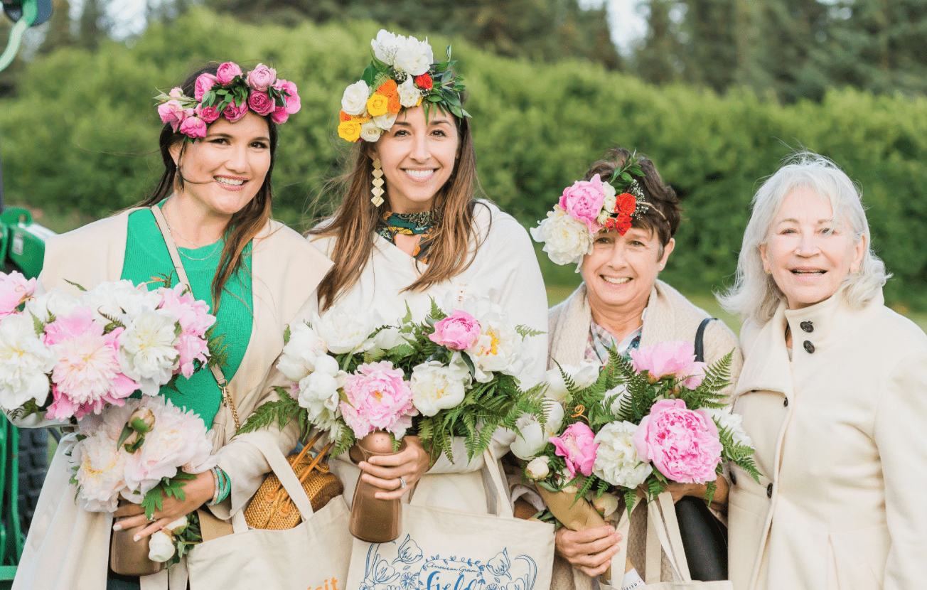 Group of four women holding flowers and swag bags.