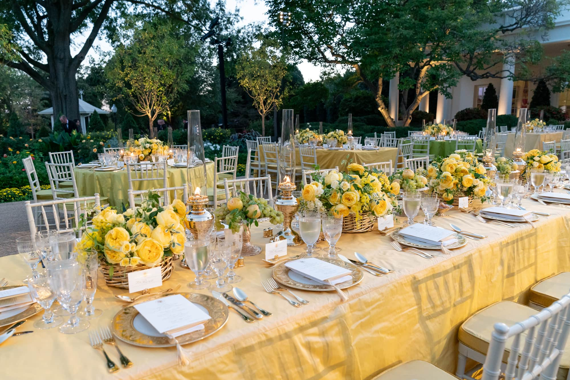 Tables set with flower arrangements and table setting for dinner in courtyard.