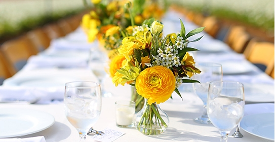View down a dinner table with yellow flower arrangements.