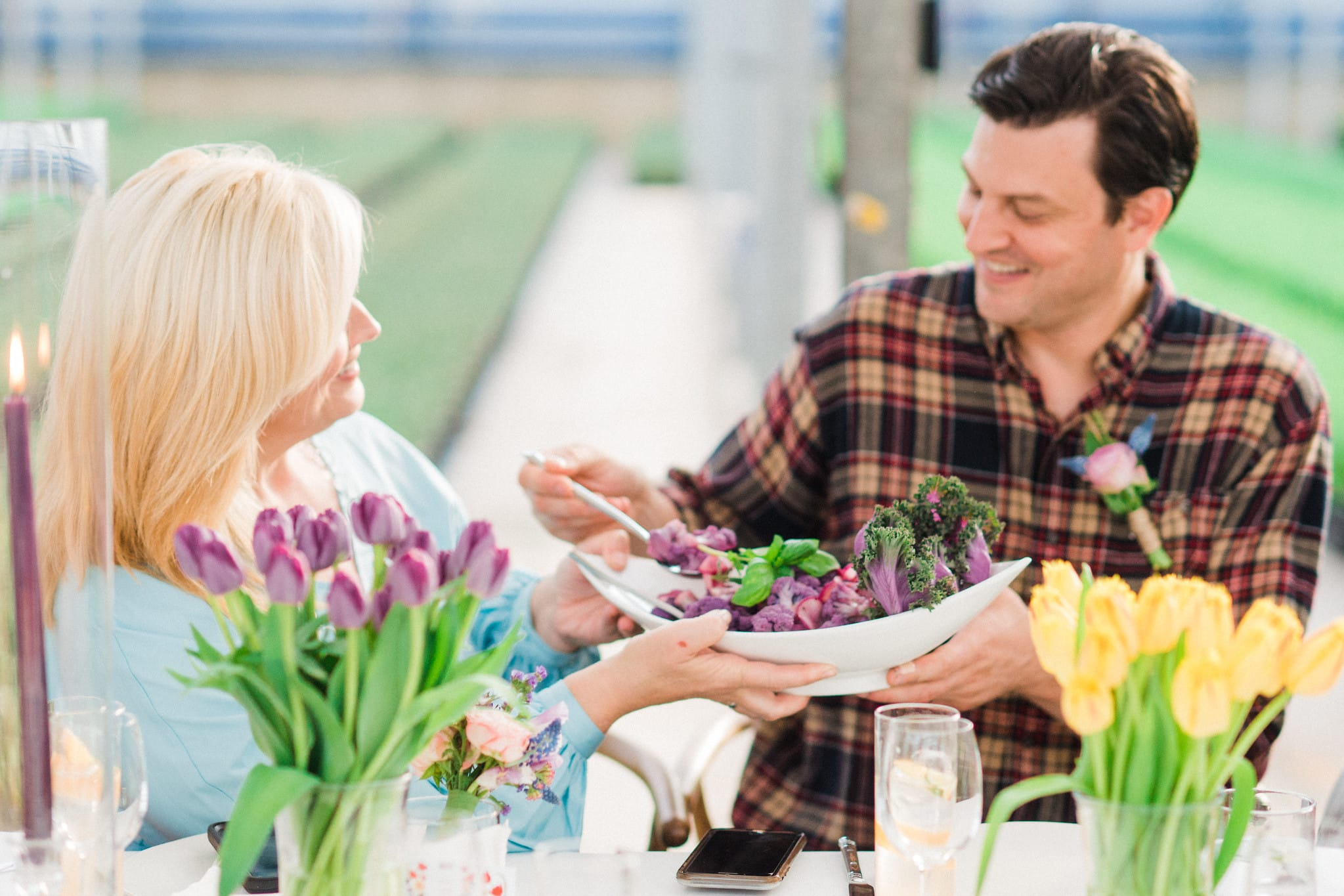 Two dinner guest is a greenhouse serving each other platters.