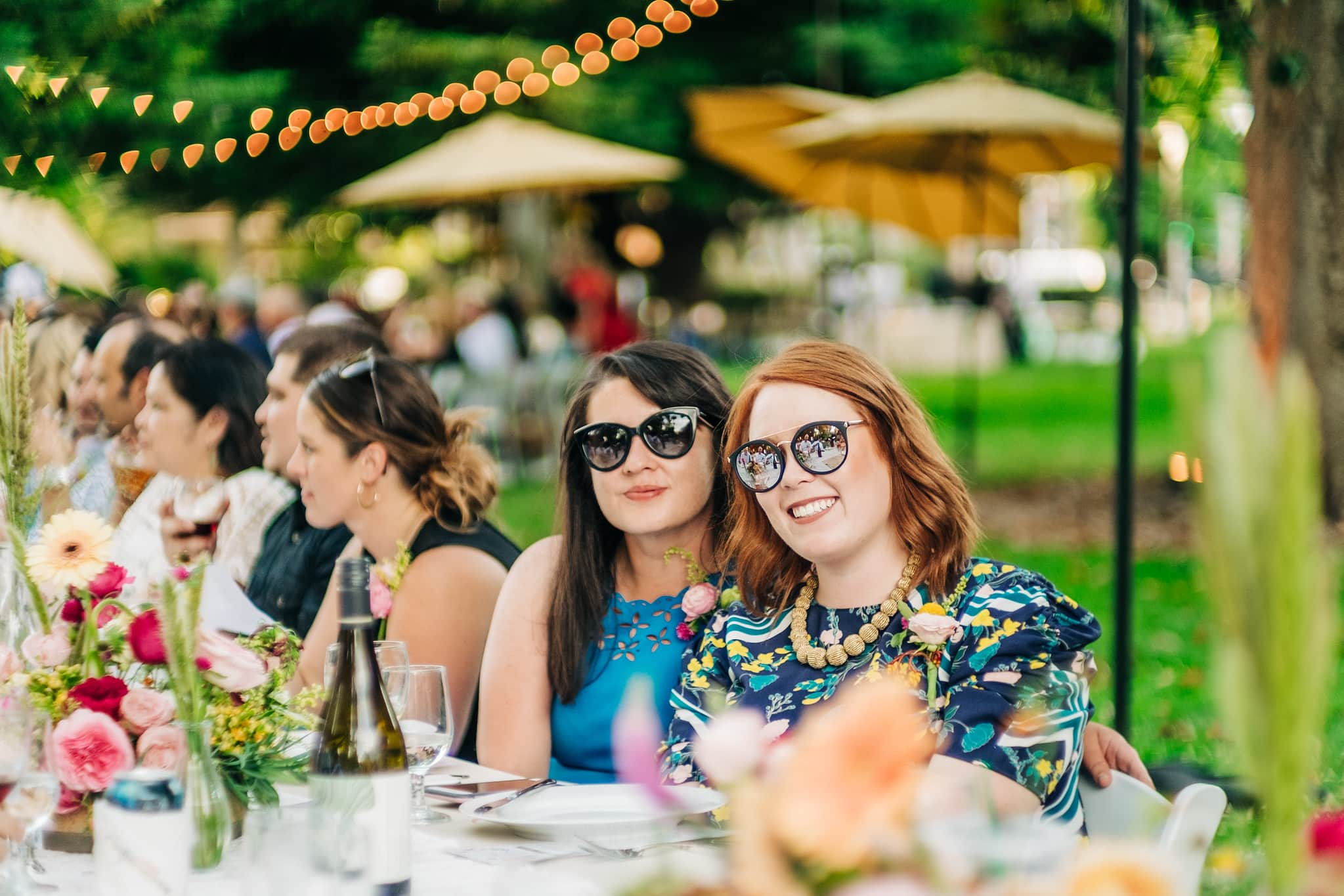 Two female guests posing at long dinner table.