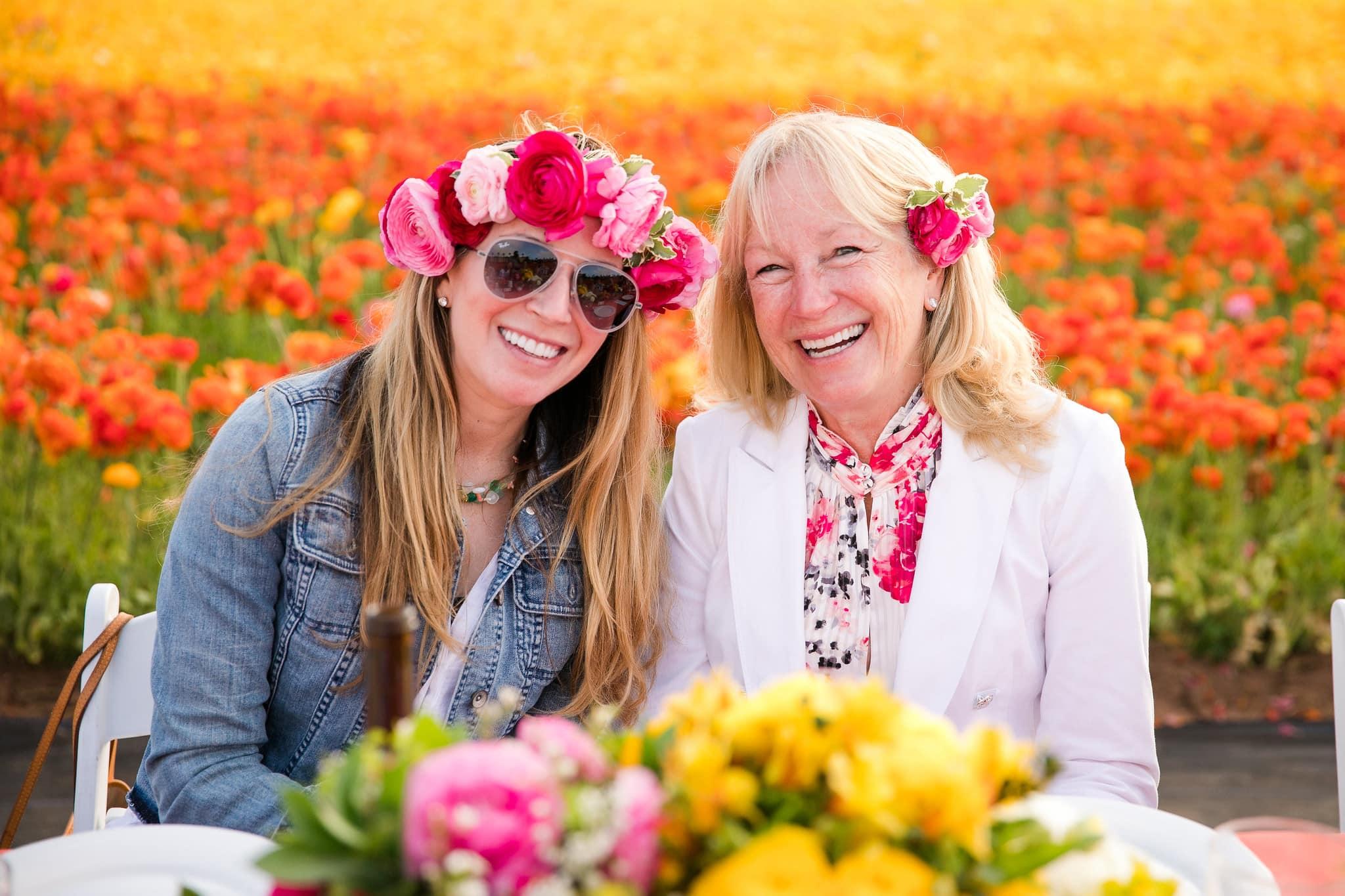 Two women sitting in front of field of flowers.
