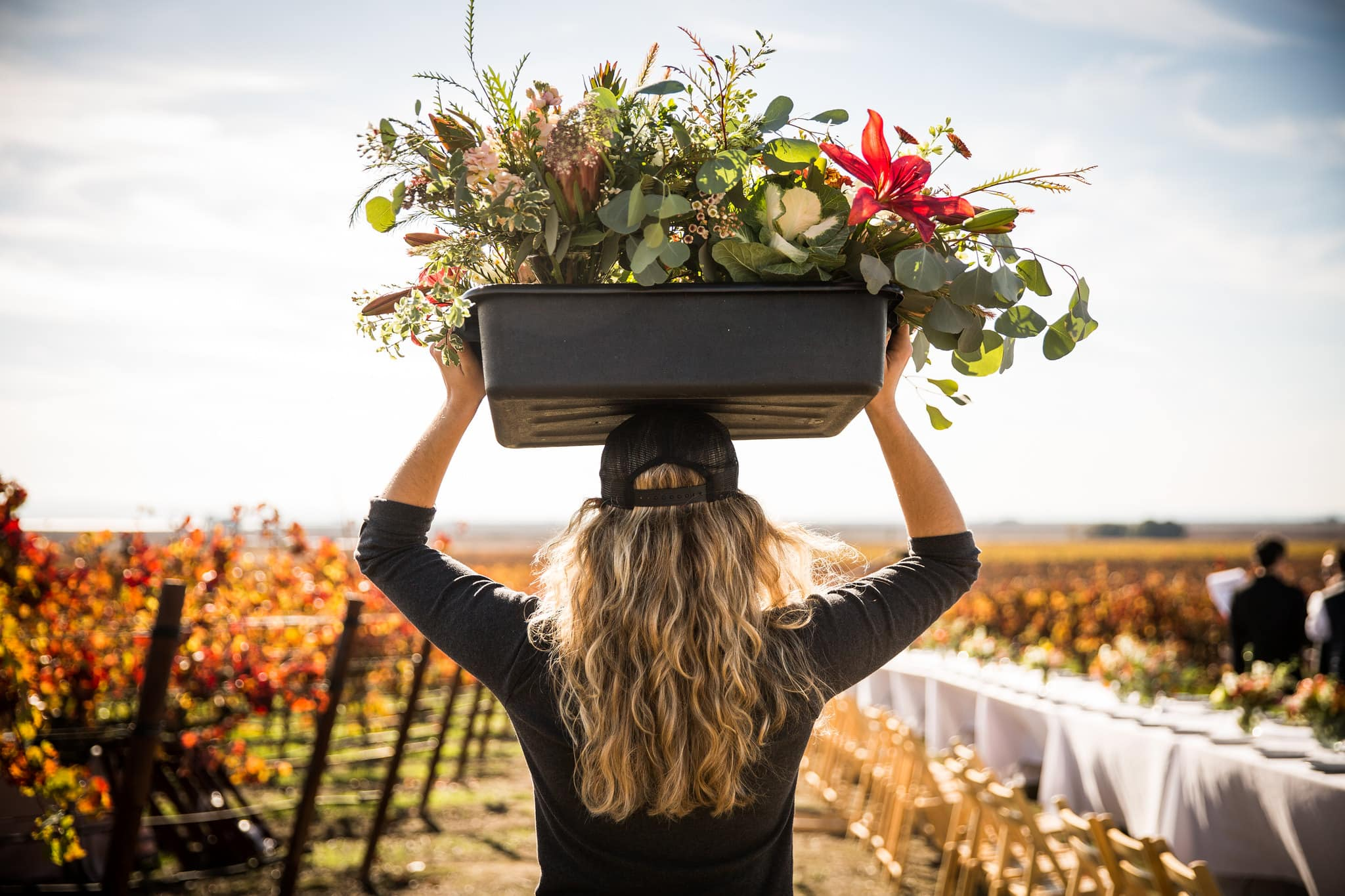 Woman carry away a bucket full of flowers.