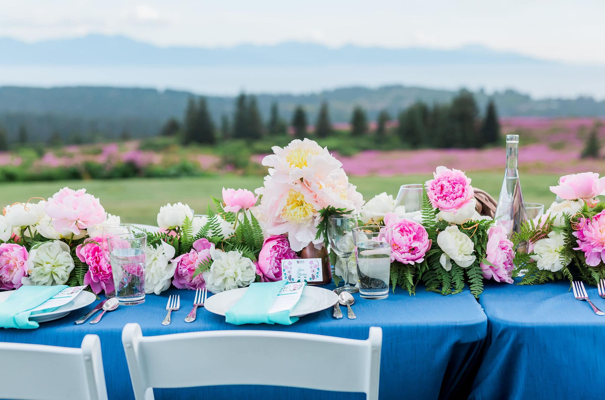 Table set with peonies in a field.