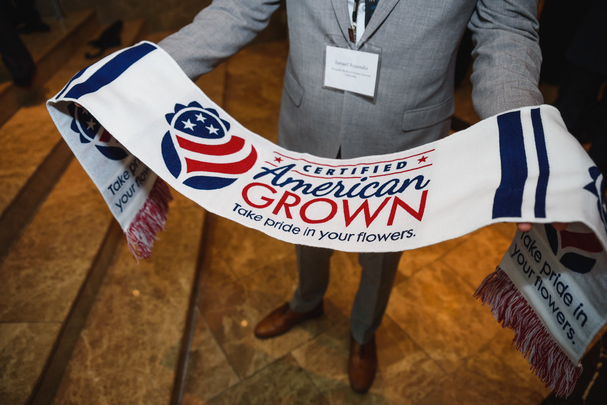 Nondescript male holding a scarf with the Certified American Grown logo.