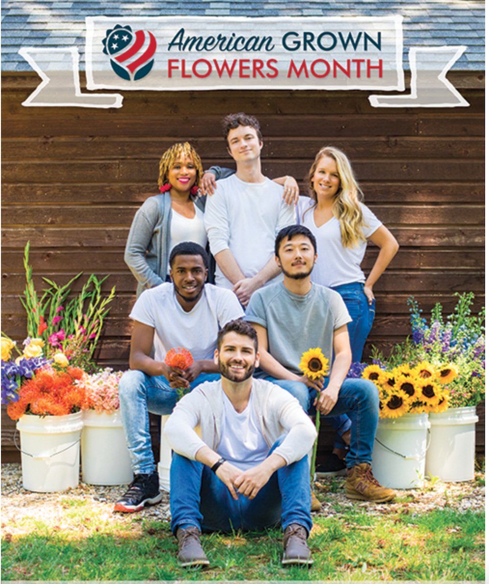 Group of young adults crouching and standing in front of a wood building surrounded by buckets of flowers.