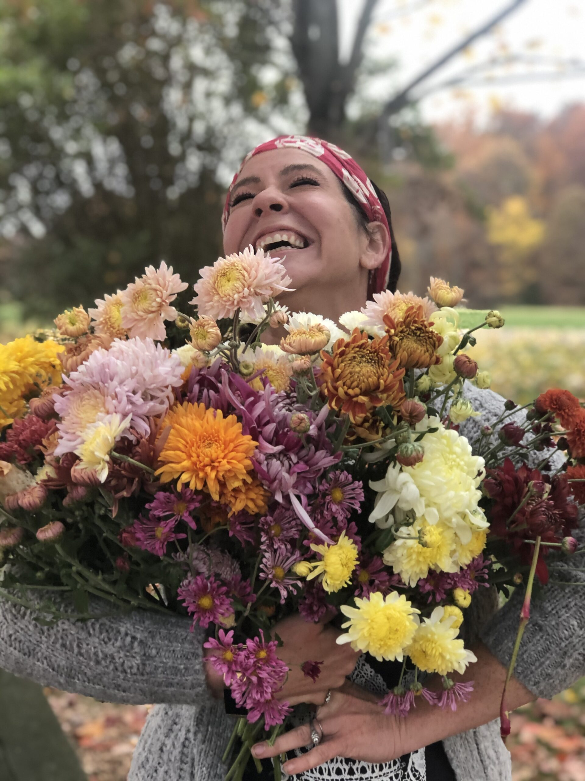 Woman holding bunches of colorful chrysanthemums.