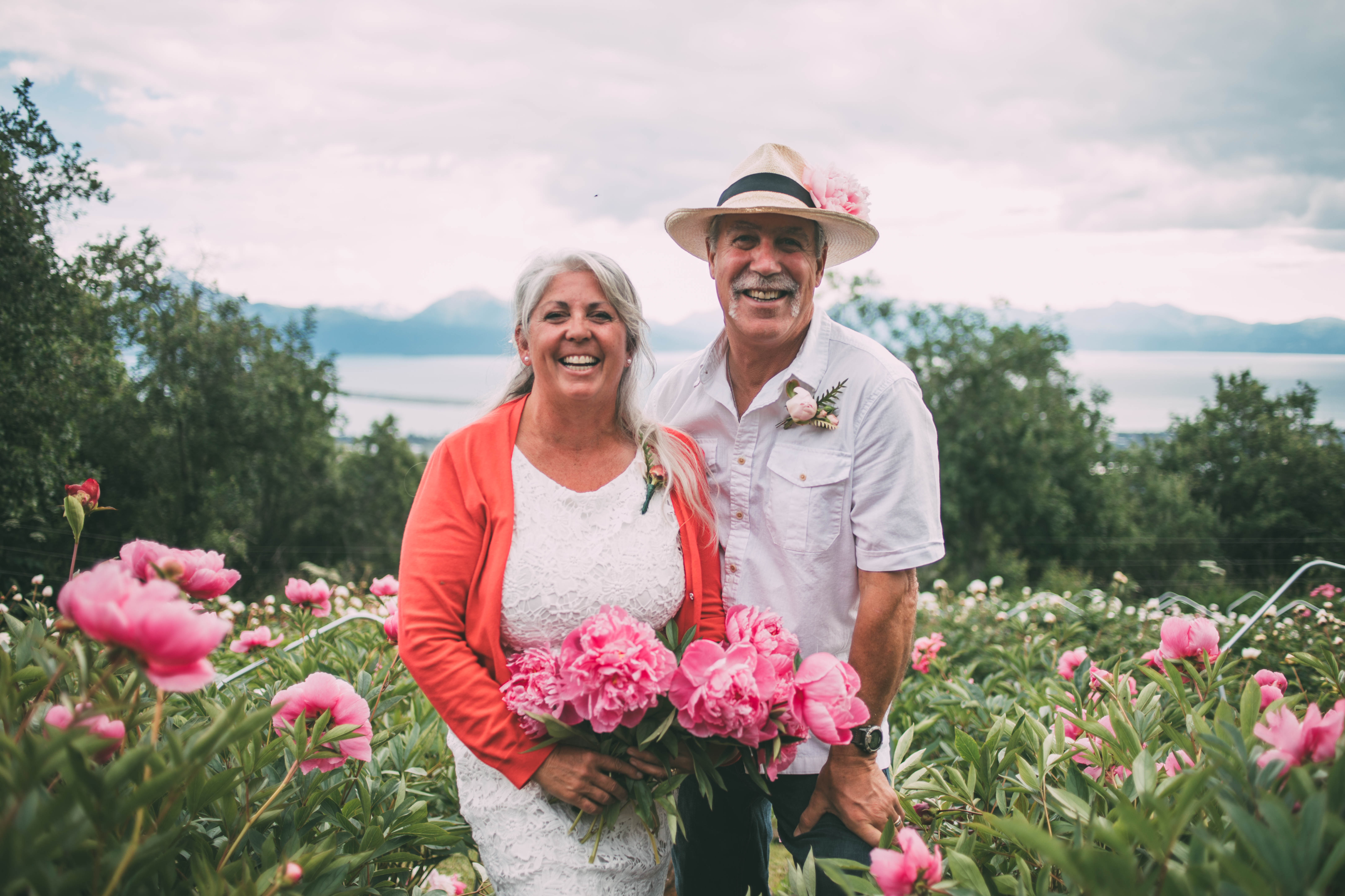 A couple holding peonies posing in peony field overlooking ocean and mountains.